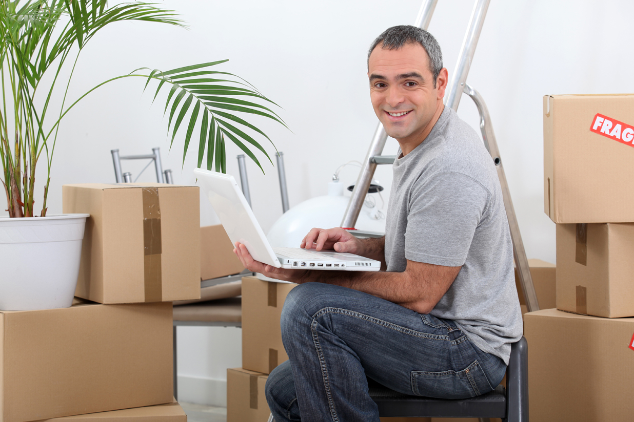 Man with laptop by boxes