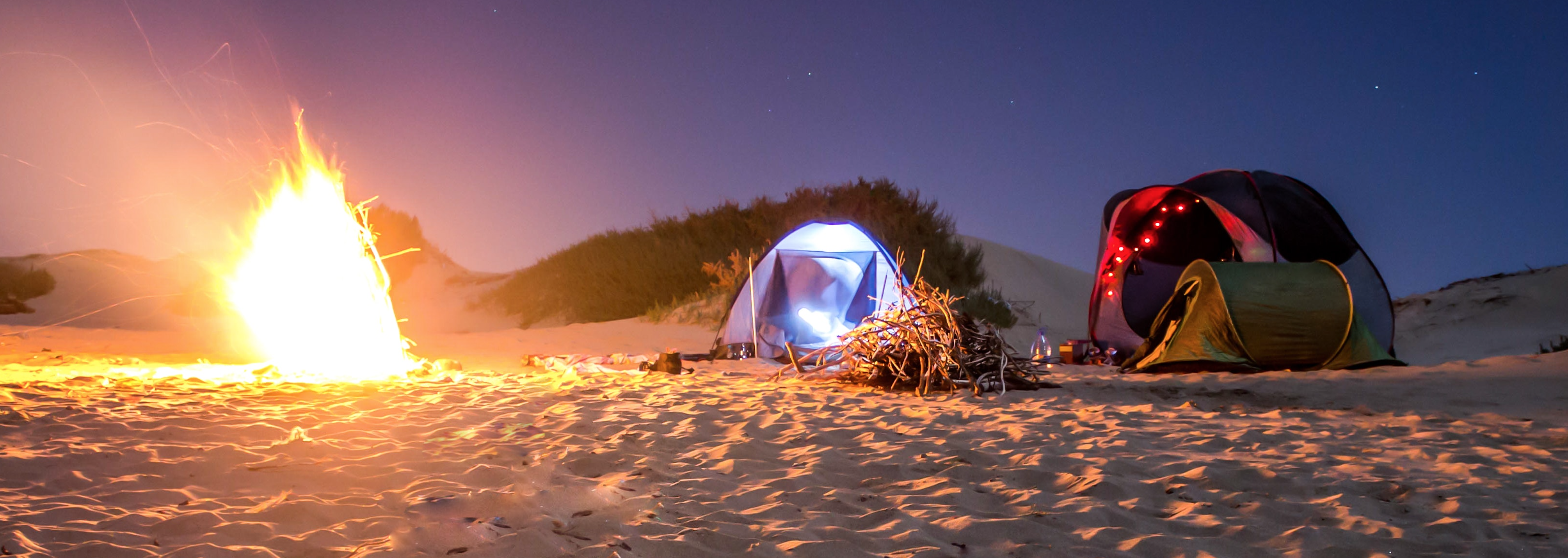 camping on beach at night with fire